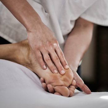 Physical therapist doing massage of male's foot