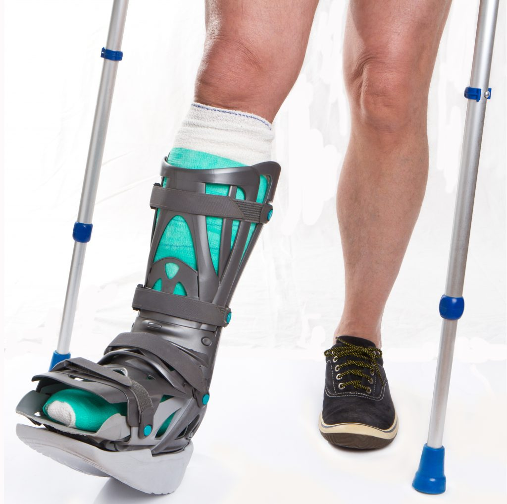Man with a broken leg with Crutches and bandage on a white background